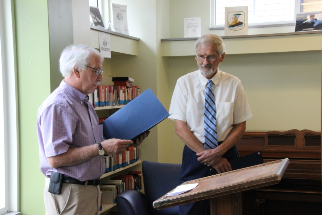West Virginia State Delegate Walter Duke (R-Berkeley, 61) reads the Certificate of Recognition presented by the Senate of West Virginia to Roger Engle at a ceremony held at Hedgesville Public Library on June 20, 2015 to honor the award-winning, West Virginia author. | Photo by Stephanie Engle