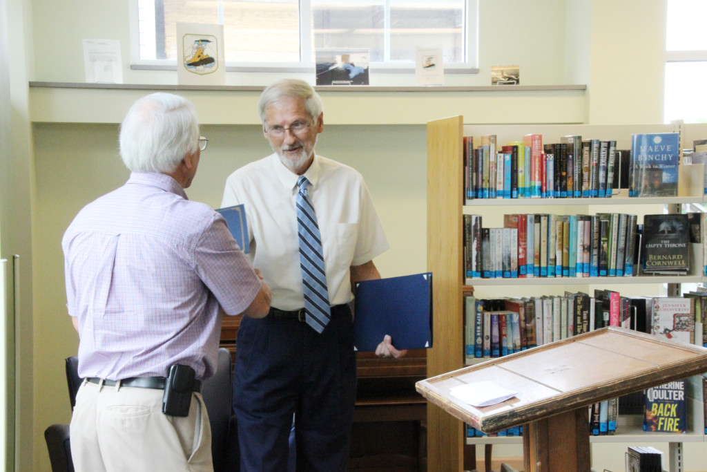West Virginia State Delegate Walter Duke (R-Berkeley, 61) presents a Certificate of Recognition from the Senate of West Virginia to Roger Engle at a ceremony held at Hedgesville Public Library on June 20, 2015 to honor the award-winning, West Virginia author. | Photo by Stephanie Engle